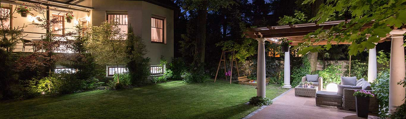 Backyard patio with outdoor lighting and a well manicured lawn