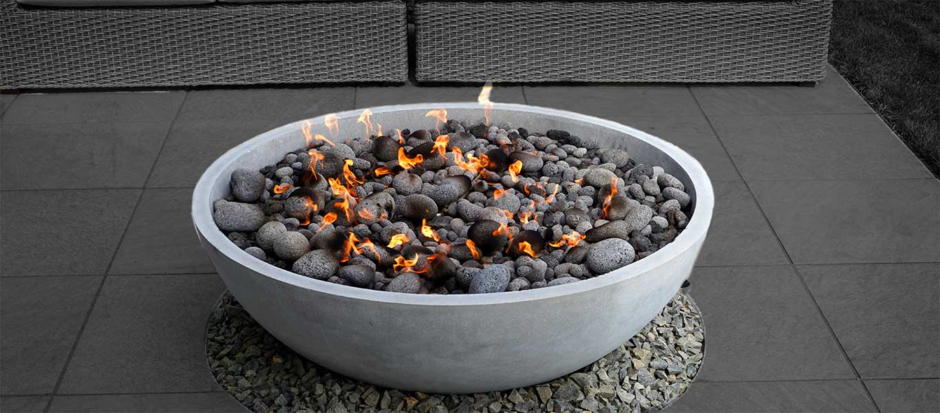elegant stone fire pit on a stone patio in the backyard